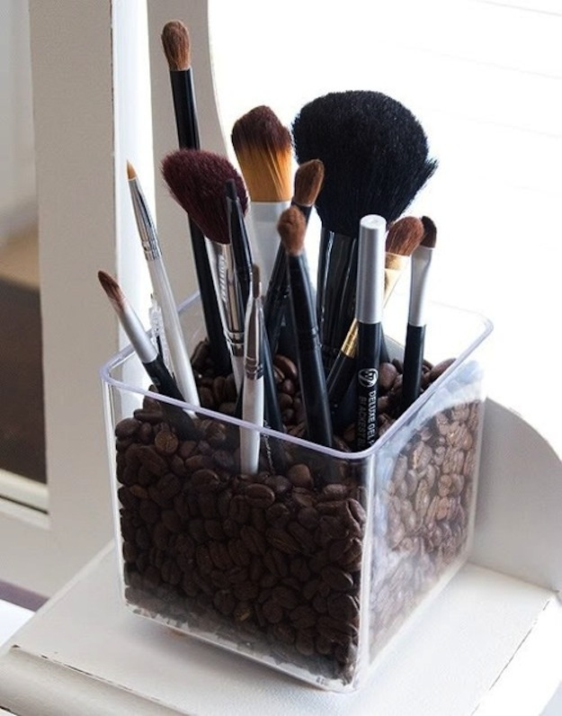 Use a candle holder filled with coffee beans to hold your makeup